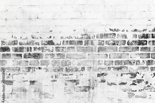Old brick wall with damaged white paint layer