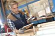 Metal worker in workshop using digital tablet