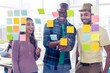 Happy business people discussing over adhesive notes