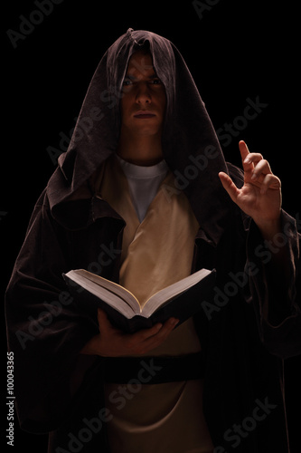 Valokuva  Mysterious monk holding a book and preaching