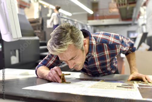 Fototapeta Man working on printing machine in print factory obraz
