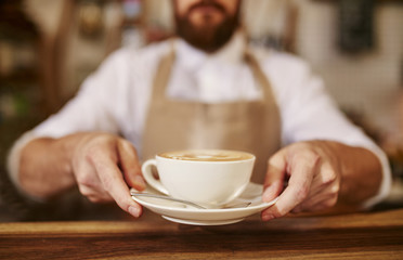 Barista serving cup of fresh coffee for you