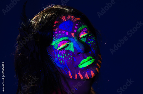 Foto op Plexiglas Art Studio Headshot woman wearing awesome glow in dark facial paint, blue based with other neon colors and obscure abstract background, facing camera