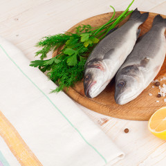 Two fresh sea bass on a white background.