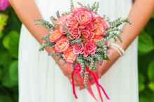 Tender Bouquet Of Coral Roses And Green Lavender In Bride's Hands