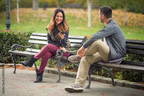 Canvas Print Two young people sitting on benches in a park and talking