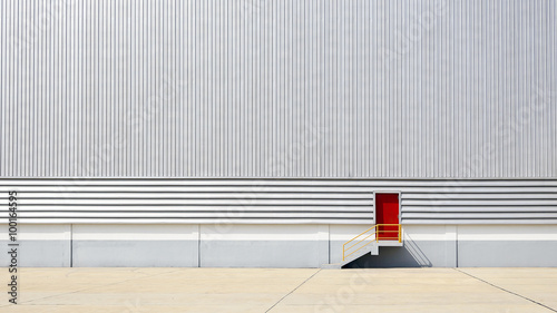 Tuinposter Industrial geb. the sheet metal factory wall with the red door entrance
