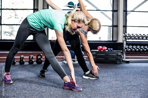 Fit women stretching in the gym - 100177946