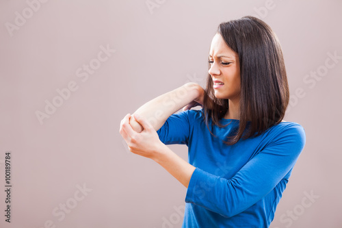 Fotografía  Portrait of young woman who is having pain in her elbow.