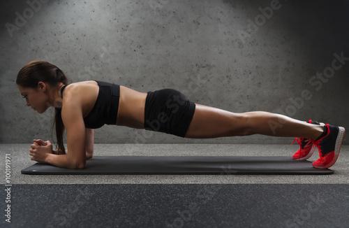 Obraz na płótnie woman doing plank exercise on mat in gym