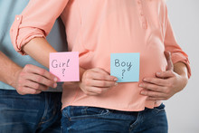 Expecting Couple Holding Paper With Girl And Boy Text