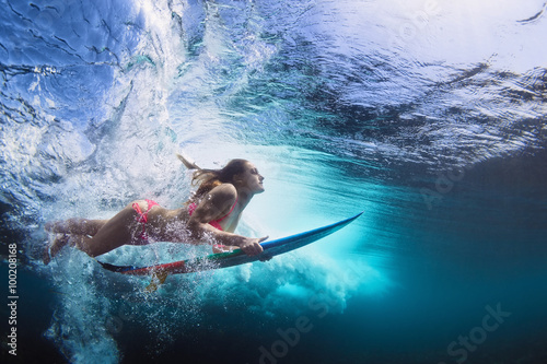 Young girl in bikini - surfer with surf board dive underwater with fun under big ocean wave Fotobehang