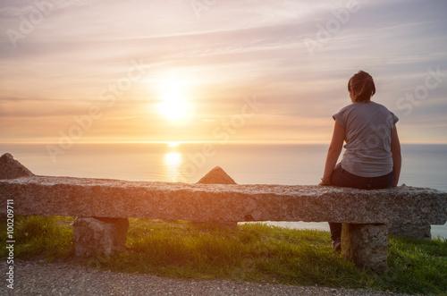 Valokuvatapetti Chica joven observando el atardecer sobre el mar en soleda