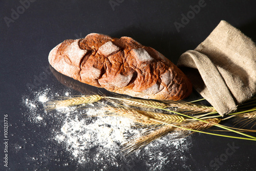 Photo Stands Egypt rustic crusty bread and wheat ears on a dark wooden table