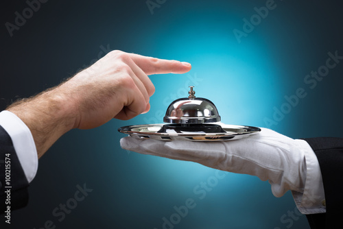 Fotografie, Obraz  Businessman Ringing In Service Bell Held By Bellboy