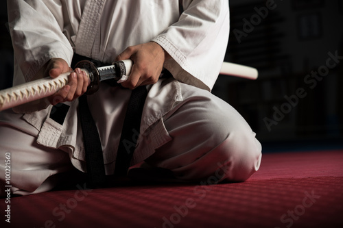 Deurstickers Vechtsport Close uo of young martial arts fighter with katana siting in seiza position