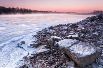 Stony bank of a freezing river covered in fog during dusk