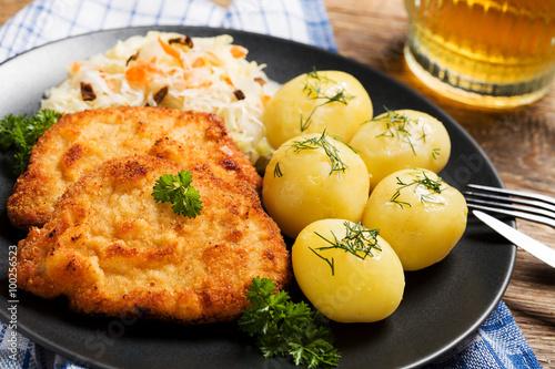 fototapeta na lodówkę Fried pork chop in breadcrumbs, served with boiled potatoes and
