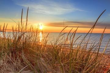 Panel Szklany Wschód / zachód słońca Dawn Of A New Day.Beautiful sunrise illuminates sand dunes and the blue water horizon as a new day begins. Port Austin, Michigan.