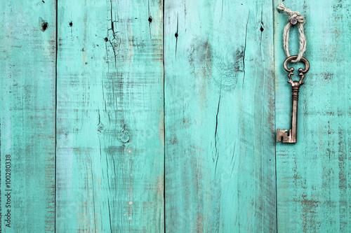 Bronze skeleton key hanging by rope on blank antique mint green rustic wood door