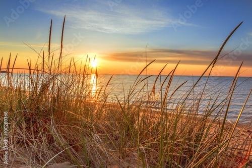 Fototapeta Dawn Of A New Day.Beautiful sunrise illuminates  sand dunes and the blue water horizon as a new day begins. Port Austin, Michigan. obraz