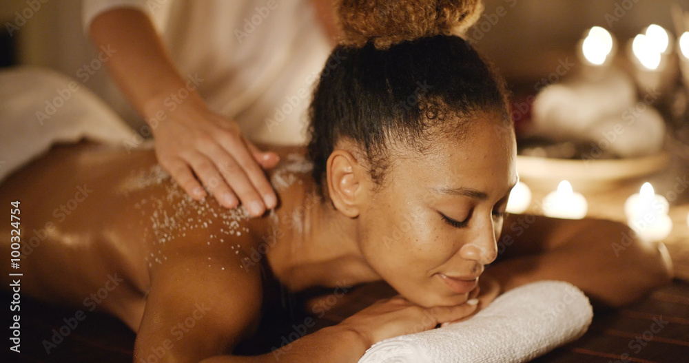 Fototapeta African-american woman getting a relaxing massage in salon in slow motion