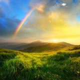 Fototapeta Rainbow - Mountain valley during sunrise. Natural summer landscape