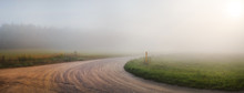 Landscape With An Old Gravel Road In The Fog. Turn Of Gravel Road. Panoramic Shot. Toned Image.