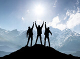 Silhouettes of team on mountain peak. Sport and active life concept..