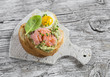 Mashed avocado sandwich with smoked salmon and fried quail egg. A delicious breakfast or snack. On light wooden rustic table