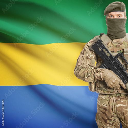 Fotografie, Obraz  Soldier with machine gun and flag on background - Gabon