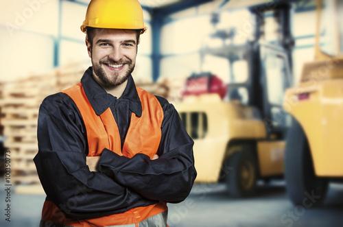 Fotografia  Smiling worker in front of forklift