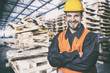 Smiling worker in protective uniform in front of wooden pallets