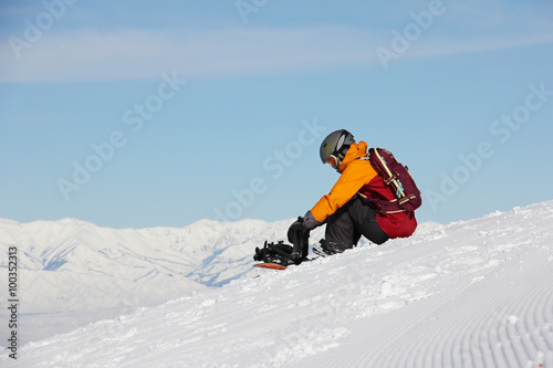 Fotobehang Wintersporten girl sitting on a slope and prepares a snowboard