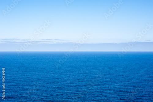 Staande foto Zee / Oceaan Deep blue empty ocean seascape with clouds on horizon