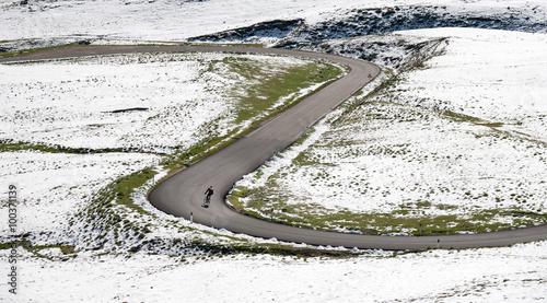 Foto op Plexiglas Fietsen Cyclist goes downhill along a mountain road in a snowy landscape. Dolomites, Italy, Europe.
