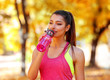 Young beautiful woman drinking water in the autumn park
