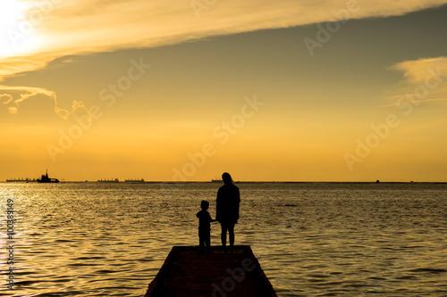 Tuinposter Pier Silhouette people under sunset sky
