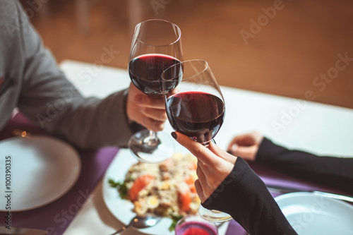 Beautiful young couple with glasses of red wine in luxury restaurant - 100390335
