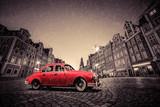 Retro red car on cobblestone historic old town in rain. Wroclaw, Poland.