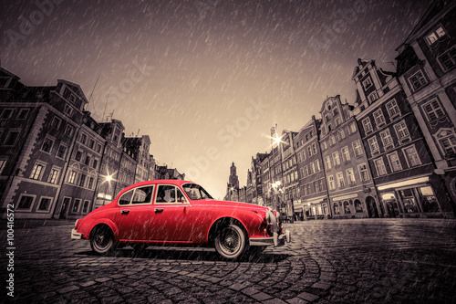 Retro red car on cobblestone historic old town in rain. Wroclaw, Poland.