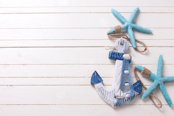 Decorative anchor and marine items on white wooden background.
