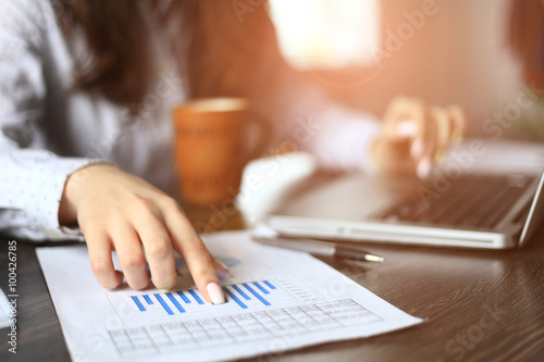 Fotografía  Hands of financial manager taking notes when working on report