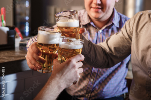 Fotografia  Happy friends drinking beer at counter in pub