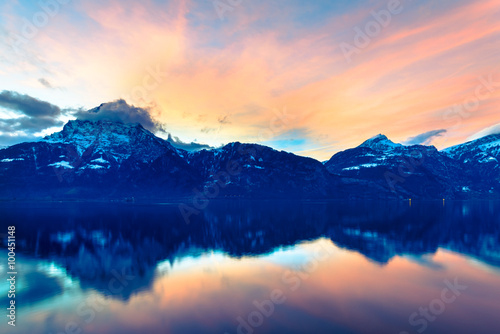 Poster Reflexion Switzerland. Mountain landscape at night. Sky is colored by the setting sun is reflected in the surface of the water.