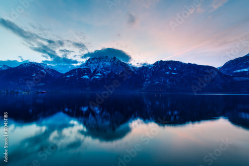 Spoed Fotobehang Reflectie Mountain landscape at night. Sky is colored by the setting sun is reflected in the surface of the water.