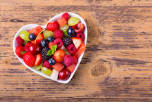 Delicious Fruit Salad In Heart Shaped Bowl On Wooden Background