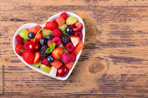 Delicious fruit salad in heart shaped bowl on wooden background Canvas Print