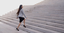 Serious Young Business Woman In High Heel Shoes Walking Up Long Flight Of Marble Stairs Outdoors