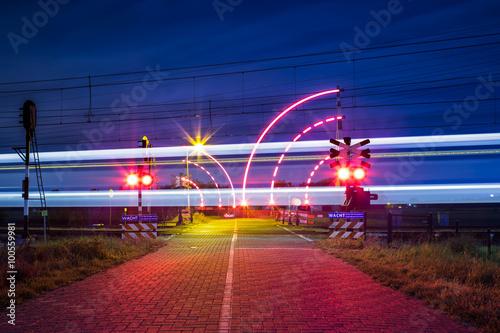 Fotografia, Obraz  Bewaakte spoorwegovergang met brandende lichten in de nacht en voorbijrijdende t
